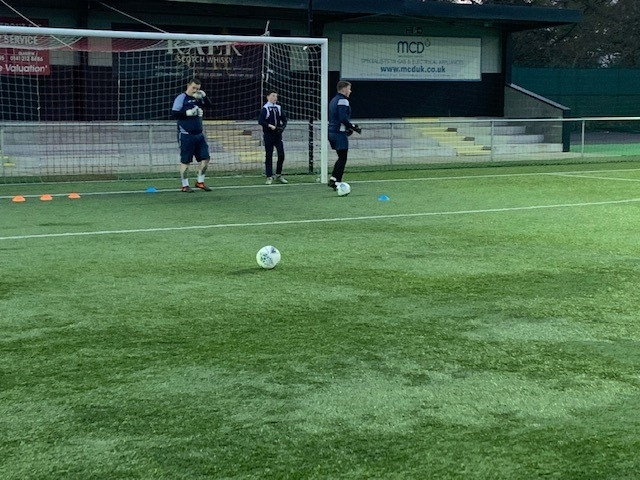 Development GK Coach Michael McCloy using Dylan Orr to demonstrate a function to Connor